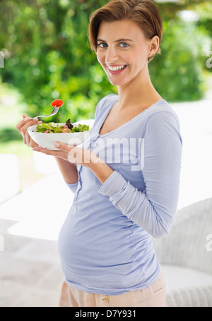 Pregnant woman eating salad - Stock Photo