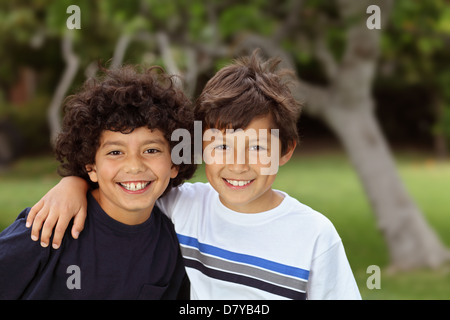 Two smiling happy young mixed race boys outside - Stock Photo