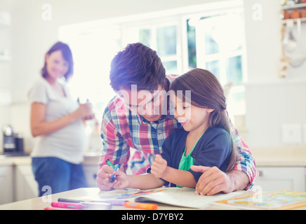 Father helping daughter use coloring book - Stock Photo