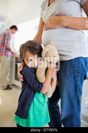 Girl hiding behind pregnant mother - Stock Photo