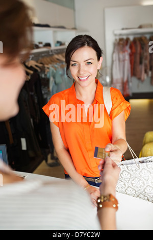 Woman shopping in clothes store - Stock Photo