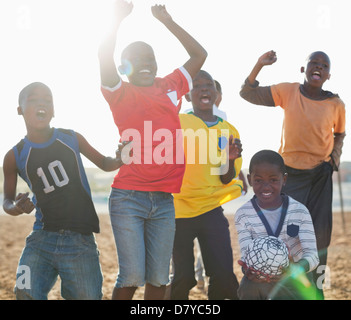 Boys playing soccer together in dirt field - Stock Photo