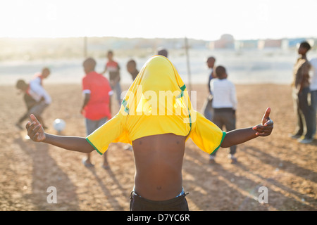 Boy celebrating with soccer jersey on his head in dirt field - Stock Photo