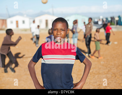 Boy standing in dirt field - Stock Photo