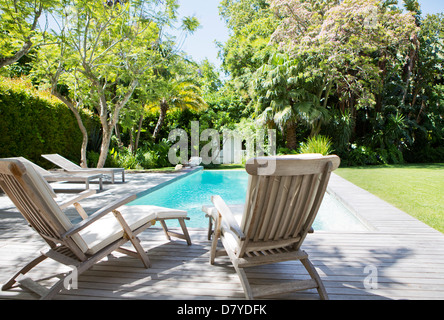 Lawn chairs and swimming pool in backyard - Stock Photo