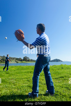 Hispanic father and son playing catch in park - Stock Photo