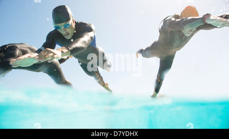 Triathletes in wetsuits running into ocean - Stock Photo