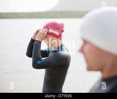 Triathletes pulling on goggles on beach - Stock Photo