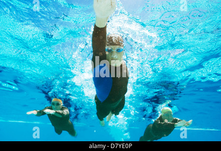 Triathletes in wetsuits underwater - Stock Photo
