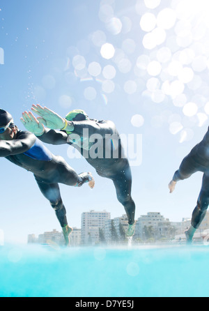Triathletes diving into swimming pool - Stock Photo