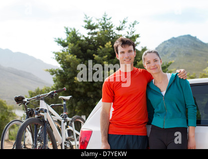 Couple smiling by car in rural landscape - Stock Photo
