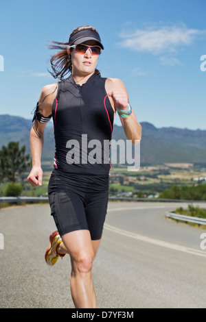 Woman running on rural road - Stock Photo