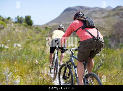 mountain bikers on dirt path - Stock Photo