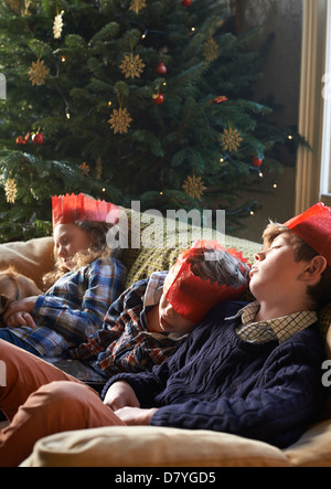 Children in paper crowns sleeping on sofa - Stock Photo