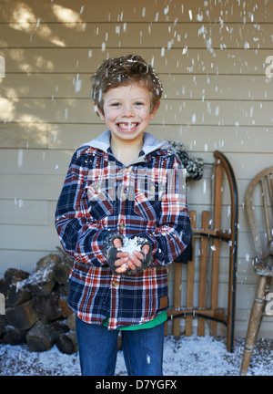 Smiling boy playing in snow - Stock Photo