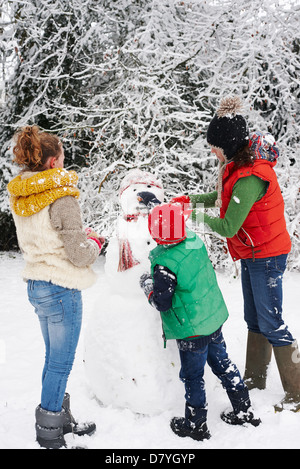 Mother and children making snowman outdoors - Stock Photo
