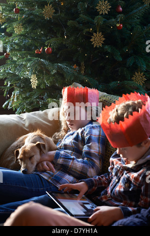 Children in paper crowns relaxing on sofa - Stock Photo