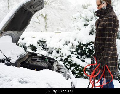Woman working on broken down car in snow - Stock Photo