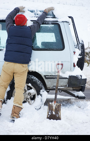 Man digging car out of snow - Stock Photo
