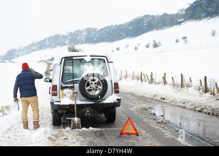 Man working on broken down car in snow - Stock Photo