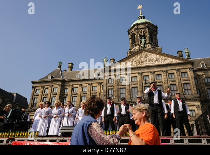 Dutch people dancing and singing in front of the Royal Palace, Dam Square, Amsterdam, the Netherlands - Stock Photo