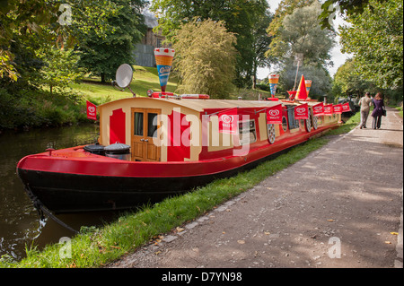 Colourful traditional barge boat moored on sunny summer day (floating shop selling ice creams) - scenic Leeds Liverpool - Stock Photo