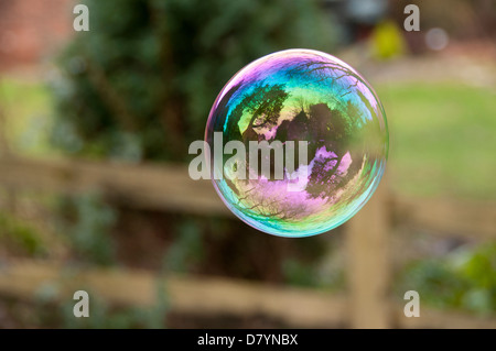 Close-up of beautiful spherical soap bubble floating in air with trees reflecting on its thin, colourful, iridescent - Stock Photo