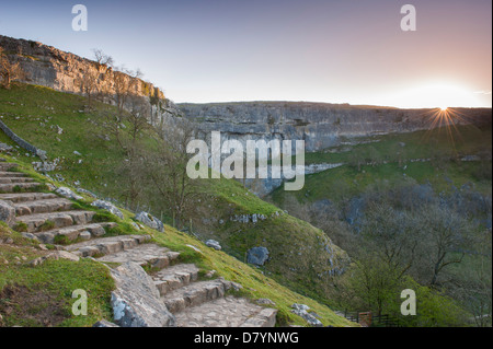 Scenic view of dramatic Malham Cove at sunset with sunburst over huge, sheer, curving limestone cliff in beautiful - Stock Photo