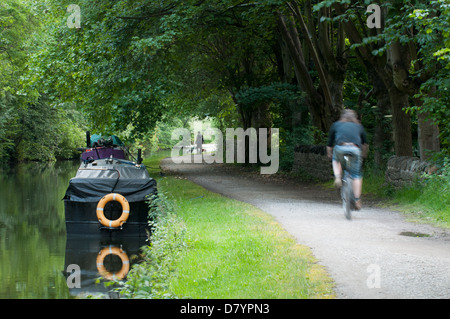 Quiet, scenic, rural, tree-lined stretch of towpath with boats moored & man cycling along - Leeds Liverpool Canal, - Stock Photo