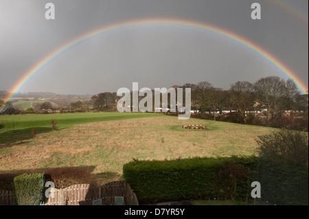 Beautiful rainbow creating a perfect arch across grey rainclouds in sky, over fields in sea-rural landscape - Baildon, - Stock Photo
