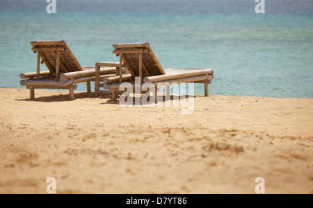 Two bamboo deck chairs in retro style on the beach - Stock Photo