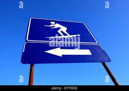 A BLUE AND WHITE SIGN INDICATING THE AREA SURFBOARDS ARE PERMITTED  TO BE RIDDEN AT THE BEACH BLUE SKY BACKGROUND - Stock Photo