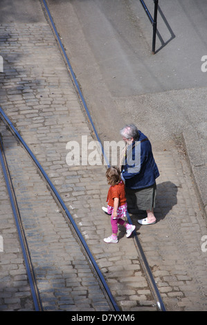 grandmother and granddaughter crossing tramlines, National Tramway Museum, Crich, Derbyshire, England, UK - Stock Photo