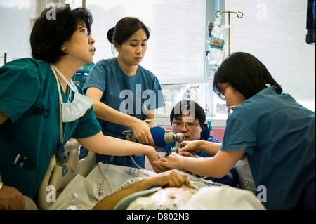 Medical staff use an oxygen tank to help revive the patient who has been under anaesthetic at the intensive care - Stock Photo
