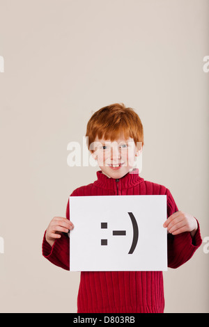 Caucasian boy holding card with smiley face - Stock Photo