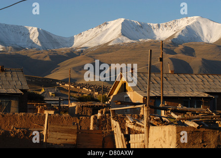 Clay houses at the sunset in the Kyrgyz village Tulek surrounded by mountains covered with fresh snow. Naryn region, - Stock Photo