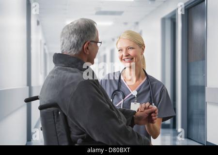 Caucasian nurse talking to patient in hospital