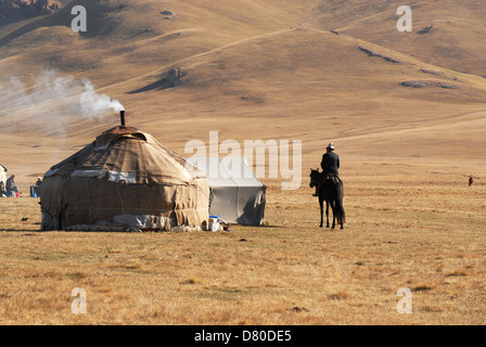Kyrgyz man riding a black horse approaches a yurt in the highland pastures at the Song Kul lake. Naryn region, Kyrgyzstan - Stock Photo