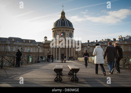 People walking on 'Pont des Arts' in Paris on a cold sunny winter day - Stock Photo