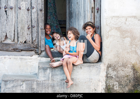 Children happily playing and laughing in doorway in Camaguey, Cuba's third largest city - Stock Photo