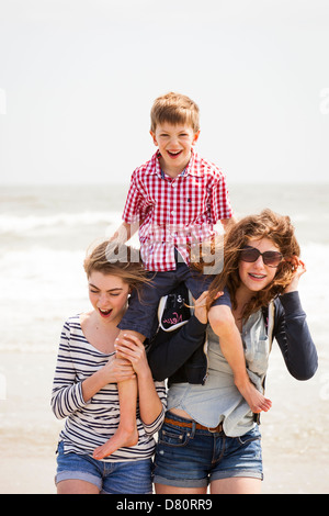 Family of 3 playing at beach - Stock Photo