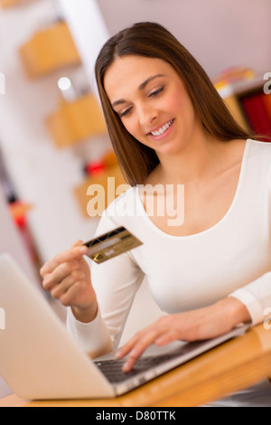 Female holding a charge card and shopping from the web on laptop - Stock Photo