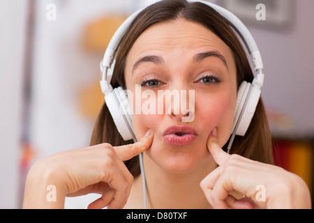 Attractive girl enjoying music through headphones, on sofa - Stock Photo