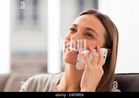 Pretty young female using white mobile phone at home smiling - Stock Photo
