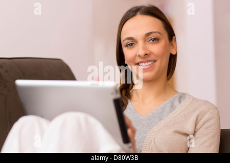 female consults email on pad, she look at the camera - Stock Photo