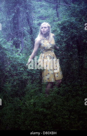 a blond girl with a yellow dress in the woods - Stock Photo