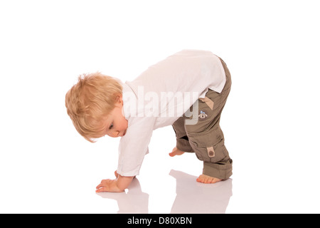 Young boy learning to walk. Isolated on white background - Stock Photo