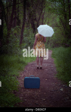 a girl with suitcase and umbrella in the woods - Stock Photo