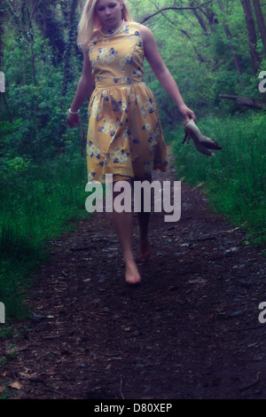 a girl in a yellow dress is running through the woods - Stock Photo