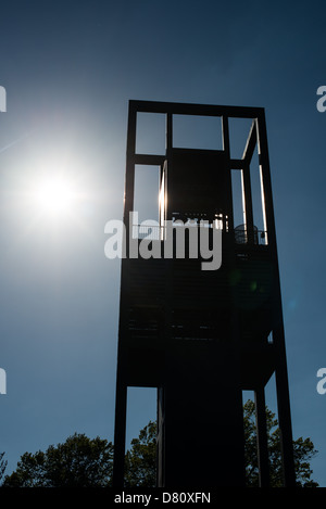 The sun silhouettes the tower at the Netherlands Carillon next to Arlington National Cemetery and the Iwo Jima Memorial. First donated in 1954, the Carillon was moved to its current location in 1960. It was a gift of the Netherlands to the United States in thanks for US aid during World War II. Stock Photo